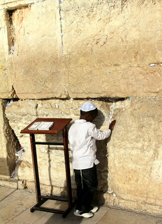 prying:  Small boy praying near Western wall  Jerusalem