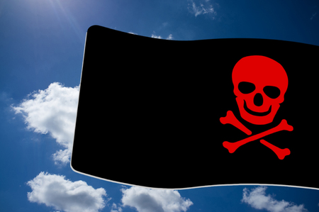 Pirate  Black Flag with red Skull and Crossbones sign on blue sky background Stock Photo