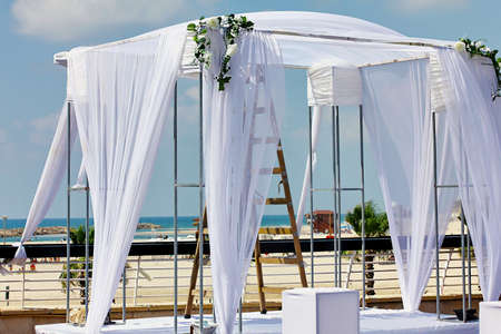 Beautiful white chuppa with white  flowers for outdoor jewish wedding ceremony photo