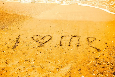 I LOVE ME  written on the sand of a beach Stock Photo