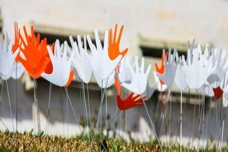 installed: Many waving abstract hands signs or flags installed on a grassy lawn using the metal wire