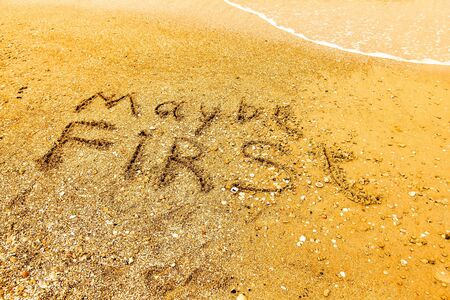 maybe: The word MAYBE FIRST written on a sandy beach in bold.