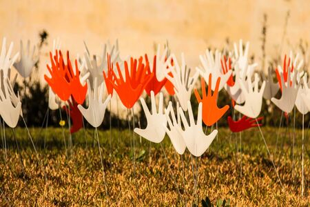 grassy: Many waving abstract hands signs or flags installed on a grassy lawn using the metal wire