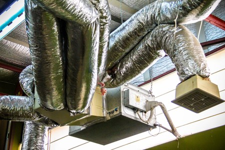 Ventilation pipes in silver insulation material under the ceiling of an industrial building