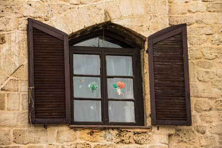 jewish home: Vintage  wooden window with shuttered  in stone wall of  Old Jaffa. Israel