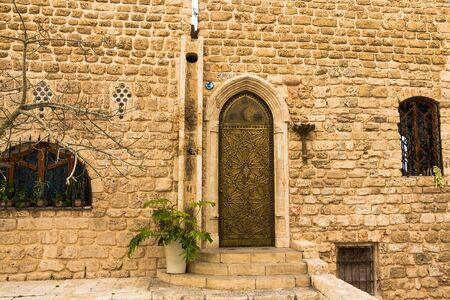 jaffo: Metal yellow  stamping door on stone wall, Jaffa, Israel Editorial