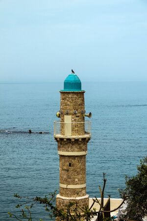holyland: The minaret of the mosque in old Jaffa   on blue sky and  Mediterranean sea background. Israel.