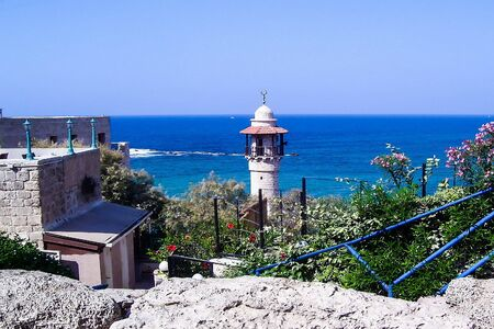 yaffo: The minaret of the mosque in old Jaffa   on blue sky and  Mediterranean sea background. Israel.