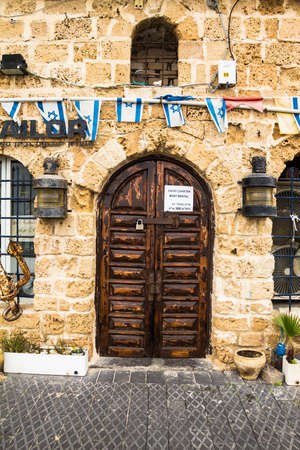 mezuzah: Announcement about renting yachts and boats for rent on the old wooden door at the port of Jaffa. Israel
