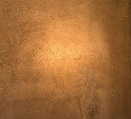 mottled: Brown painted  plaster pattern  background with spotlight and  place for your design or text