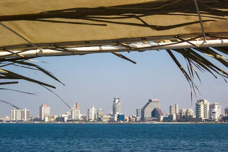 sukkot: Skyline of Tel Aviv  from pleasure boat decorated for the holiday of Sukkot. Israel