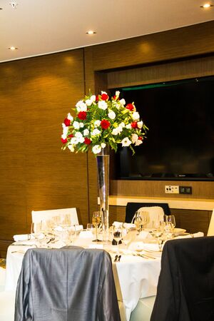 ceiling plate: Wedding banquet  hall in shades of white with  beautiful flowers in vase and two mens jackets hanging on the backs of chairs