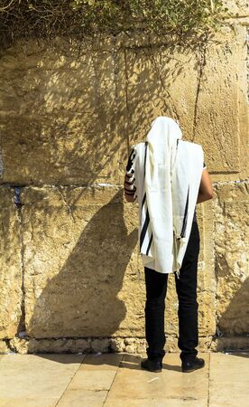 Unidentified jewish worshiper in  tallith and tefillin praying at the Wailing Wall an important jewish religious site. Jerusalem. Israel Stock Photo