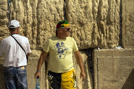 bandana western: Unknown tourist in yellow shorts and a bright yellow colored bandana on his head at the Western Wall. Jerusalem. Israel Editorial