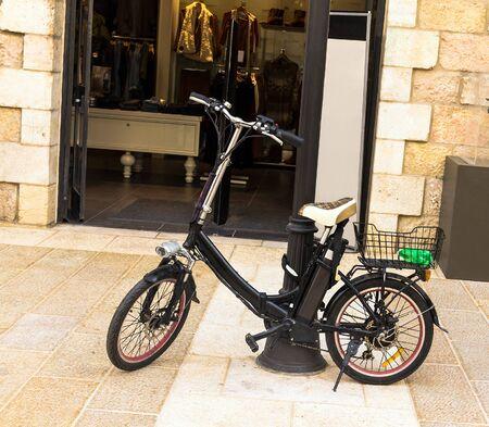 Electric bike near  open door of shop Stock Photo