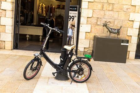 batteries: Electric bike near  open door of shop  at Mamilla Street in Jerusalem. Israel