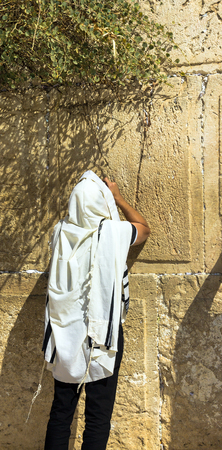 kippah: Unidentified jewish worshiper in  tallith  praying at the Wailing Wall an important jewish religious site. Jerusalem. Israel