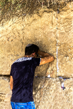 Unidentified young jewish worshiper in skullcap   praying at the Wailing Wall an important jewish religious site. Jerusalem. Israel Editorial