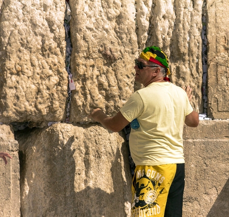 lays down: Unknown tourist in yellow shorts and a bright yellow colored bandana on his head lays down a note into a crack in the Western Wall. Jerusalem. Israel