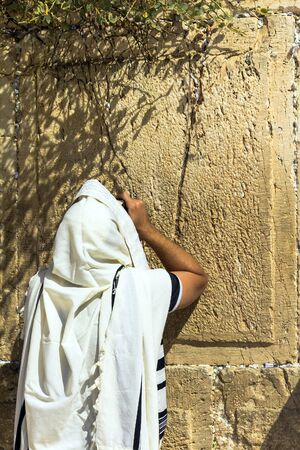 mishnah: Unidentified jewish worshiper in  tallith  praying at the Wailing Wall an important jewish religious site. Jerusalem. Israel