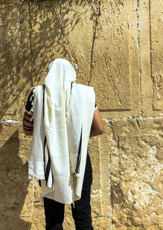mishnah: Unidentified jewish worshiper in  tallith and tefillin praying at the Wailing Wall an important jewish religious site. Jerusalem. Israel Stock Photo