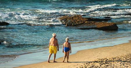 80 years: Elderly  80 years old couple makes an evening walking along the seashore. Tel Aviv. Israel