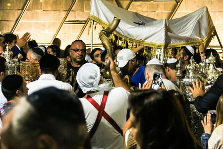 simchat torah: Unidentified  people near Bible scrolls during the ceremony of Simhath Torah listen to the sound of the Shofar, jewish religious instrument. Tel Aviv. Israel Editorial