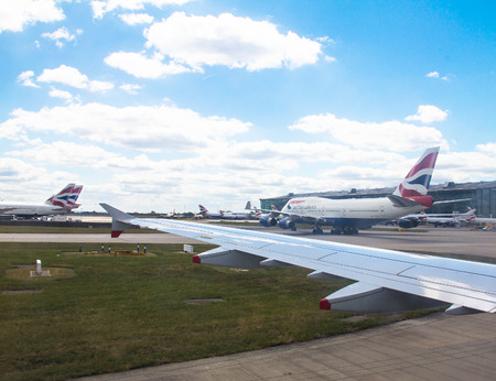 747 400: Rullaggio aereo Airbus A-320 dopo l'atterraggio in aeroporto di Heathrow vicino British Airways jet aereo passeggeri Boeing 747-400 su sfondo cielo poco nuvoloso. Londra. UK