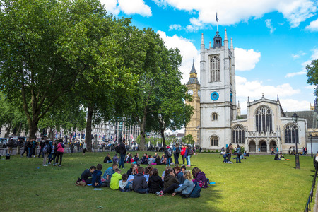 coronation: Unidentified tourists resting on the grass near Westminster Abbey, traditional place of coronation and burial site for English monarchs. London. UK