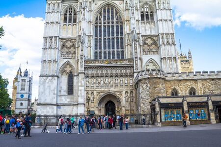 st  peter: Unidentified tourists near University Church of St Peter at Westminster Abbey on blue sky background. London. UK