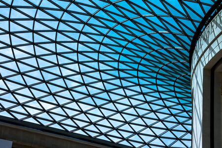 glass ceiling: The British Museum glass ceiling. Museum was established in 1753, largely based on the collections of the physician and scientist Sir Hans Sloane. crown on top of the pillars on blue sky background. The Mall street. London. UK