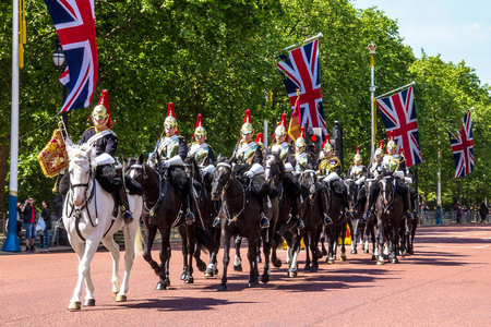 ceremonial clothing: Household Cavalry walk along The Mall in London, England, towards Buckingham Palace. The parade of the Horse Guards is very popular with visitors. crown on top of the pillars on blue sky background. The Mall street.