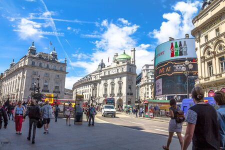 tdk: View of Piccadilly Circus with unidentified tourists and locals in London. Billboards famous brands have been here for at least 20 years and are considered symbols of famous square. crown on top of the pillars on blue sky background. The Mall street. Lond Editorial
