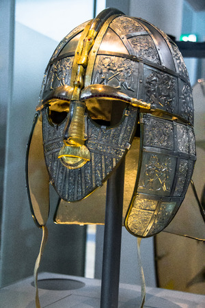 woodbridge: Replica of the helmet. The helmet and mask are part of the Sutton Hoo Treasure which was kept at the British Museum. The picture is of a replica, with the original find further down together with more artifacts from antiquity. London, UK Editorial