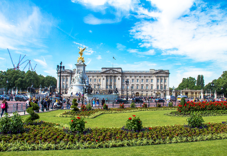 queen victoria: Tourists gather at the gates of Buckingham Palace and the base of the Victoria monument. The flag flies to show the queen is in residence. London, UK Editorial