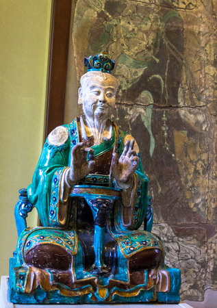 polychrome: Daoist Detty. Ming Dynasty1488-1644 in British museum. London. The seated figure of a Daoist detty holding a black pearl in his right hand, polychrome glazed porcelain from Shanxi Province