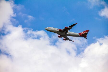 jumbo jet: Boeing 747 Virgin Atlantic gaining altitude after takeoff  from  Londons Heathrow airport. Plane is wearing new livery announced in early 2011.  Boeing 747 is popularly called Jumbo Jet. London, UK
