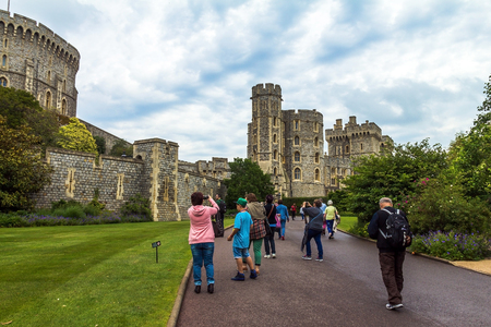 the royal county: Unidentified visitors near medieval buildings inside Windsor Castle. Windsor Castle is a royal residence at Windsor in the English county of Berkshire .  Windsor,UK