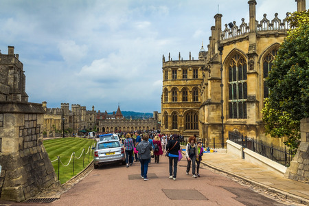the royal county: WINDSOR, ENGLAND - JUNE 5, 2015: Unidentified tourists near St. George Chapel in Windsor Castle, royal residence at Windsor in the English county of Berkshire.
