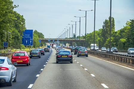 Intensive left-hand traffic on British three lane motorway M4   with active electronic overhead information sign at grey cloudy  summer day. London, UK