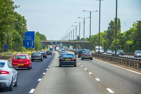 Intensivo de tráfico a la izquierda en la autopista británica de tres carriles M4 con signo electrónico activo de información aérea en gris nublado día de verano. Londres, Reino Unido