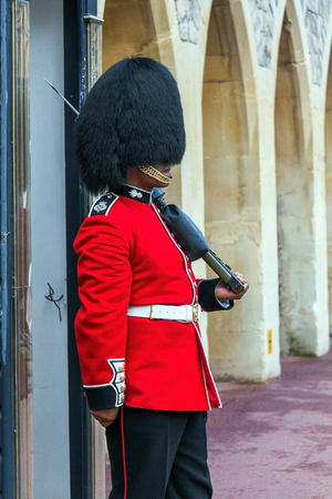 residences: Unidentified Queens Guard  in a traditional uniform preparing to be on duty at the post inside the Windsor castle. The Queens Guard is the contingents of infantry and cavalry soldiers charged with guarding the official royal residences. UK