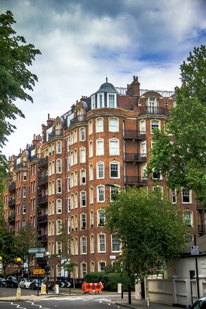 notting hill: Old  large apartment red brick houses on Addison Road in Kensington Olympia district, London, England, United Kingdom. Addison Road is a road ,which connects Kensington High Street with Notting Hill and Holland Park Avenue and runs nearby to Holland Park.