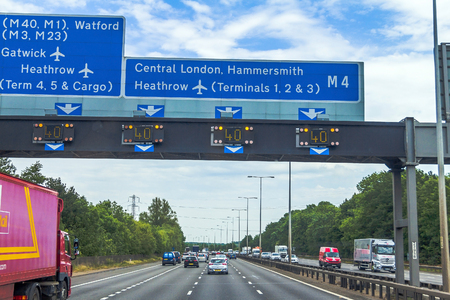 Intensive left-hand traffic on British four lane motorway M4 between Windsor and London  with active electronic overhead information sign at grey cloudy  summer day. UK