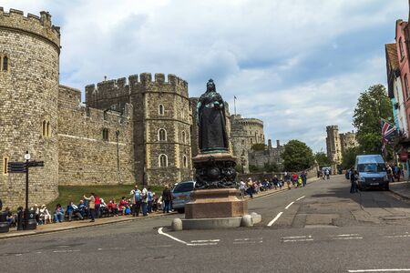 plinth: Unidentified tourists near  Lower Ward in medieval Windsor Castle and statue of Queen Victoria on a plinth in the road  in the  County of Berkshire. UK