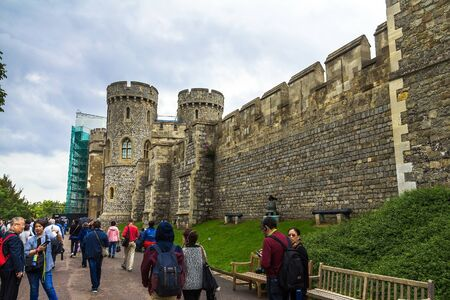 donjon: Unidentified visitors near Donjon   or Edward tower - the great tower or innermost keep of a Medieval Windsor Castle. Windsor Castle is a royal residence at Windsor in the English county of Berkshire. It was built in 1066 by William the Conqueror and it i Editorial