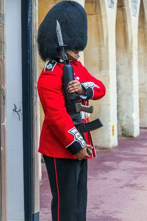 charged: Unidentified Queens Guard  in a traditional uniform preparing to be on duty at the post inside the Windsor castle. The Queens Guard is the contingents of infantry and cavalry soldiers charged with guarding the official royal residences. UK