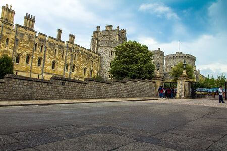 prince charles of england: Panoramic view of stone walls, buildings and towers of Windsor  Castle. and unidentified tourist. UK