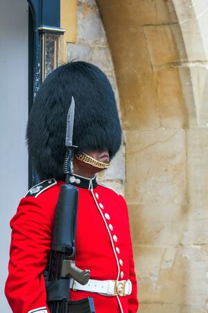 charged: Unidentified  British Queens Guard in a traditional uniform stands  on duty at Windsor Castle.  The Queens Guard is the contingents of infantry and cavalry soldiers charged with guarding the official royal residences. UK