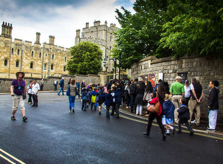 windsor: Unidentified visitors queuing in front of the  medieval Windsor Castle. Windsor Castle is a royal residence at Windsor in the English county of Berkshire. UK
